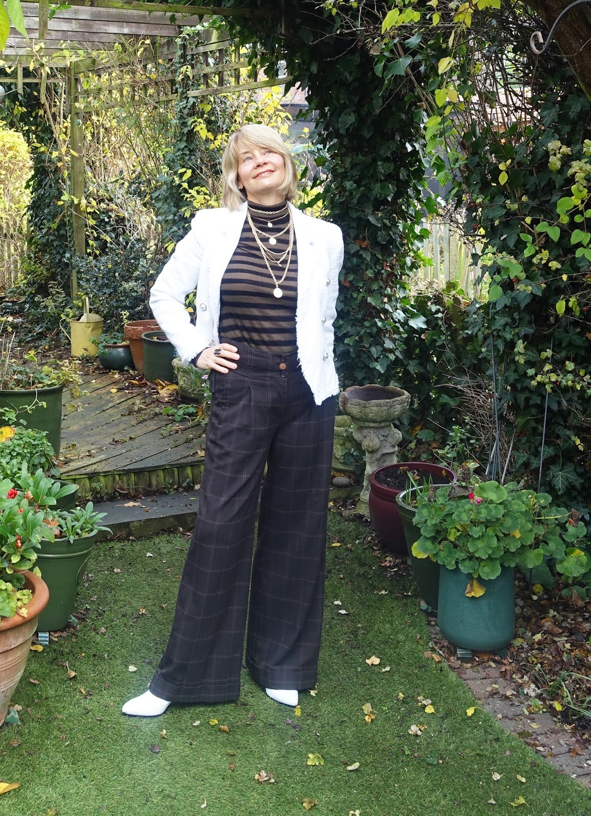 Is This Mutton the style blog for the over-50s dusts off a pair of 1990s brown parallel check trousers and brings them up to date with a mock neck jumper and layered coin necklace.