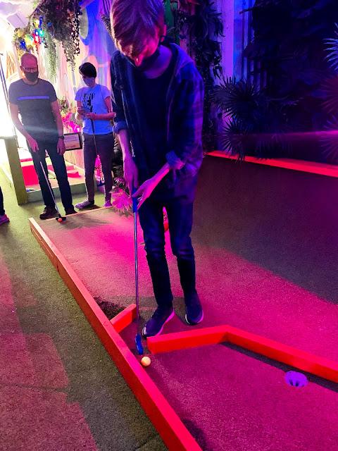 Teenager playing crazy golf at Plonk, Camden Market, London