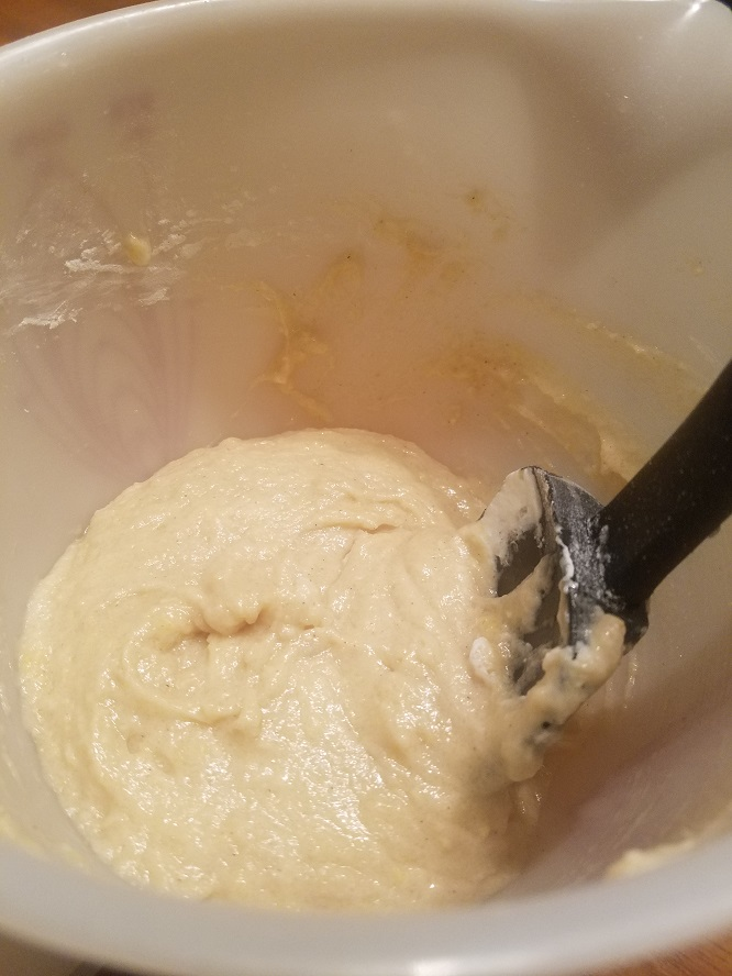 this is a sour cream donuts batter in a white bowl and black spatula in it