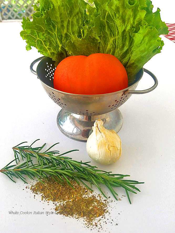 Fresh herbs and vegetables in a metal colander