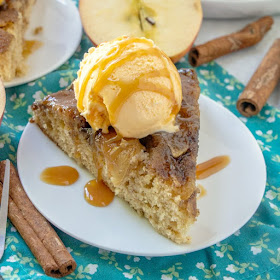 close slice of warm upside down caramel apple skillet cake with scoop of ice cream and drizzle of caramel sauce