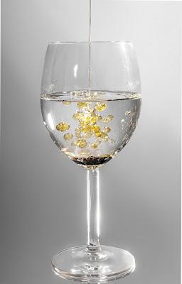 水が入ったガラスコップに油を注ぎ込む