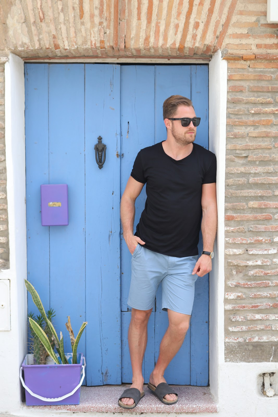 Man wearing black top and blue shorts standing against blue door in Tarifa, Spain