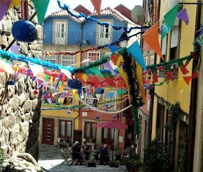 Ruela do Porto com enfeites de São João e pessoas numa mesa