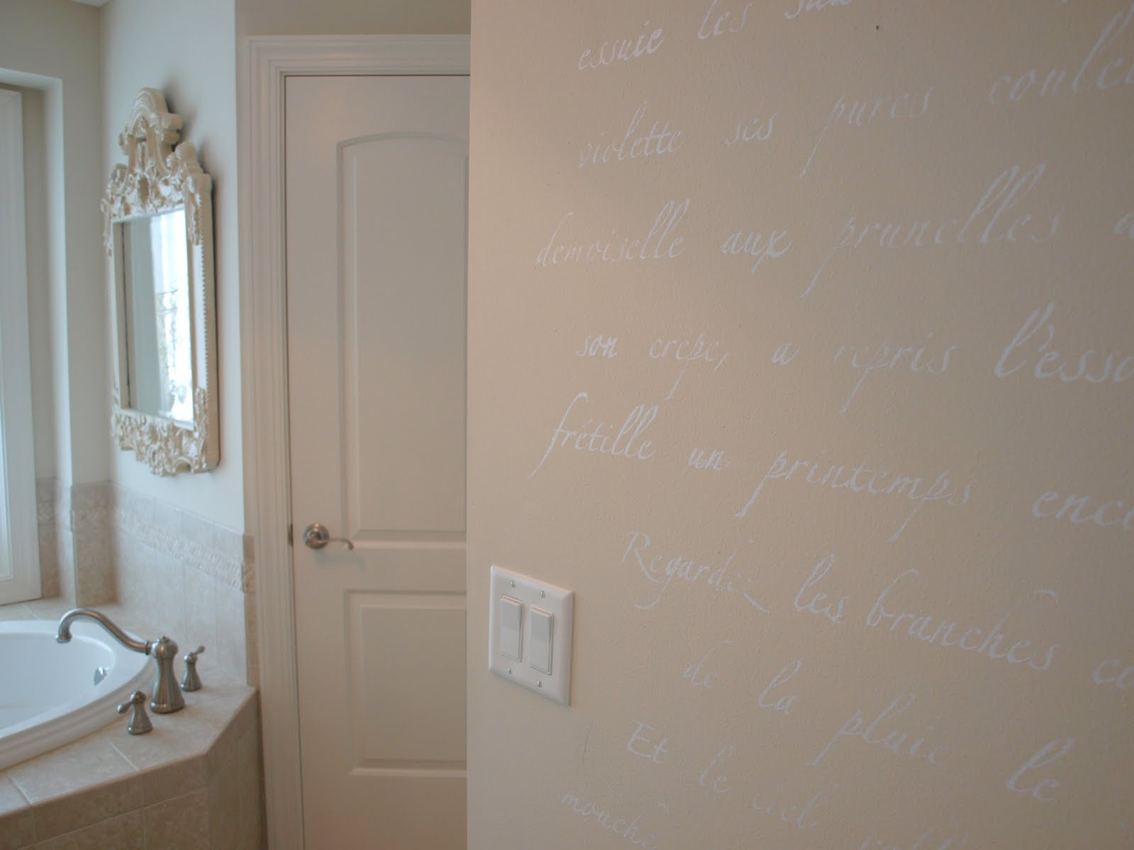 Springtime in Paris script stencil by Royal Design Studio was used on wall of bathroom by Hello Lovely Studio.