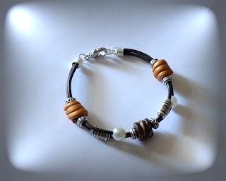 f0b90bff16d7 Pulsera con abalorios hechos de arcilla dorada y marrón. Además lleva como  adornos perlas y entrepiezas de zamak. El cierre es un mosquetón de plata.