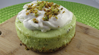 4 inch pistachio cheesecake on a crust with pistachio and homemade whipped cream then topped with more pistachios