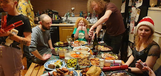 Christmas dinner in my household. Hectic scene with people putting food and crackers on the table, and a boy in the middle grinning with double thumbs up