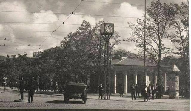 """1927 год. Перекресток бульваров Бастея и Бривибас. """"Часы Вецкалнса"""" с четырьмя циферблатами на железной оси возле Колоннадного киоска - трамвайной остановк"""