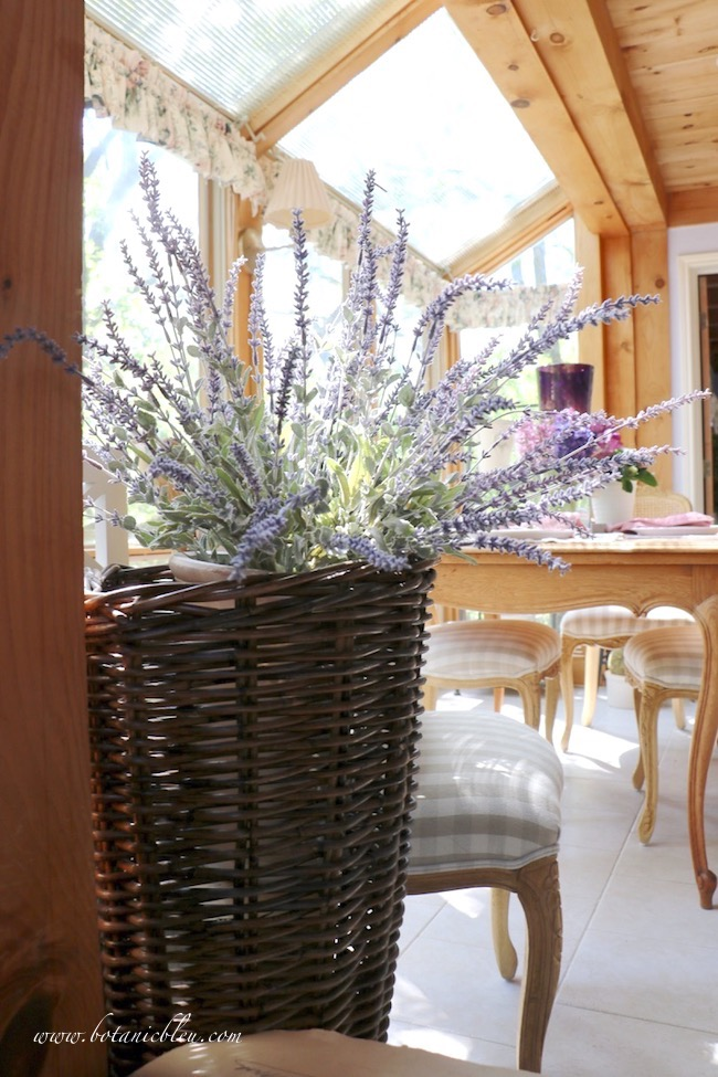 Realistic faux French lavender in a French market basket adds French Country style to a breakfast room in a sunspace