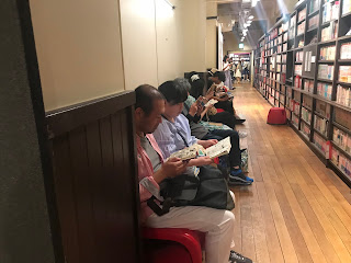 Wall of shelves with people seated before them reading
