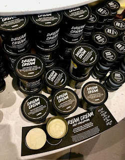 A selection of black cylindrical tubs with dream cream in white font with white cream inside with a rectangular black plaque that says dream cream on a large rectangular light brown shelf on a bright background