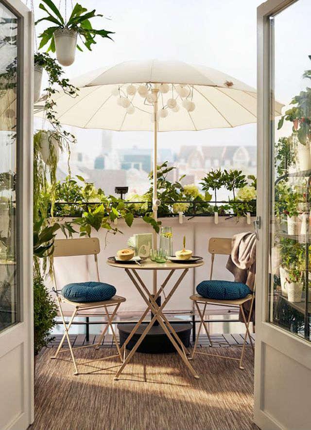 Pequeño balcón con mesa y sillas plegables y sombrilla