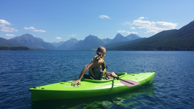 Girl looking at the mountains in her green kayak