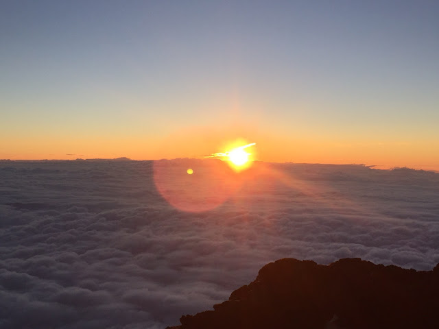 Clouds in the foreground with the orange rays of the sun spilling out