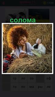 на соломе лежит девочка и играет с кроликом белого цвета