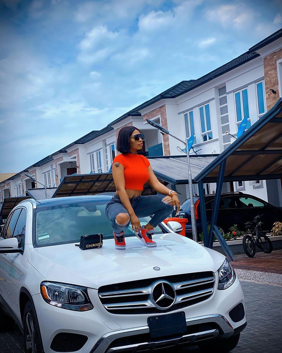 Reality star, Mercy Eke poses with her white benz [photos]