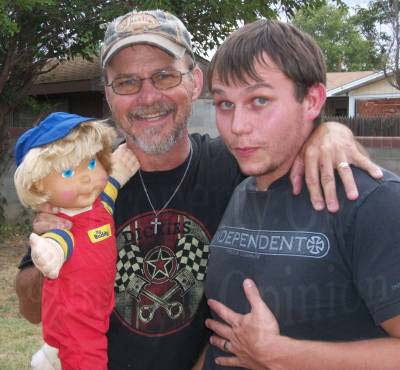 Jimmy holding a My Buddy doll while holding his son Tim with arm around back of neck