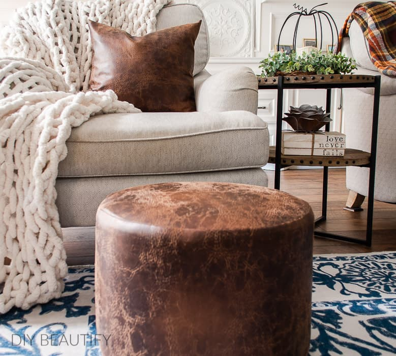 brown leather ottoman and pillow
