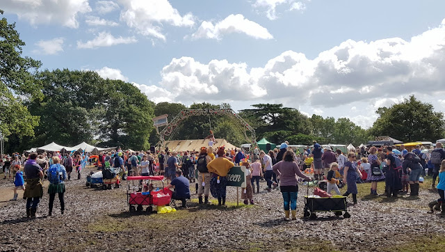 Village Green at Just So Festival 2019 Saturday afternoon 6 inch deep in thick mud but with lots of people watching trapeze artist