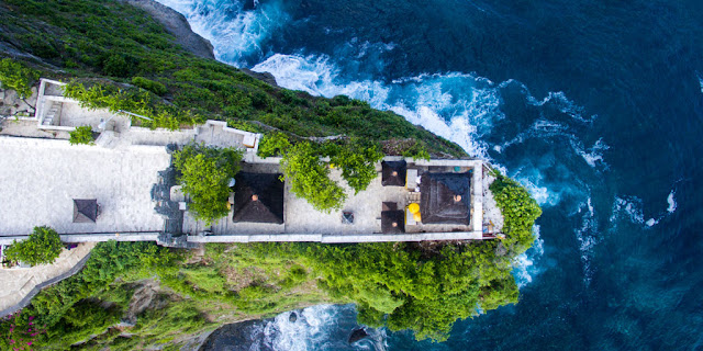 Enjoy the Beauty of Luhur Uluwatu Temple on the Edge of a Towering Cliff with an expanse of the Blue Sea below