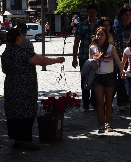 senhora com cravo vermelho na mão e balde com cravos aos pés oferecendo para uma menina que passa