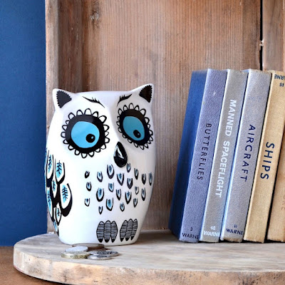 owl-shaped money box with bright blue eyes