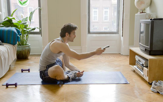 Man sitting watching tv with weights by his side | www.thefittestblogger.com