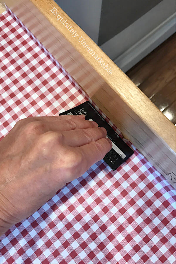 Using a credit card to smooth out red checked contact paper in a drawer