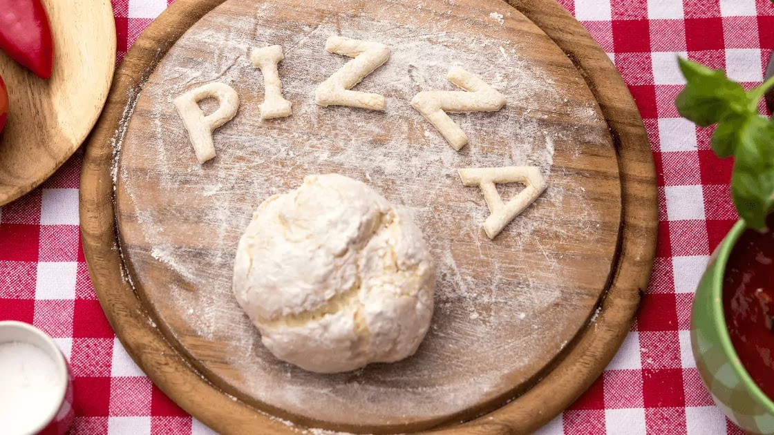 The word pizza is written in letters of cut pizza dough over a wooden circle