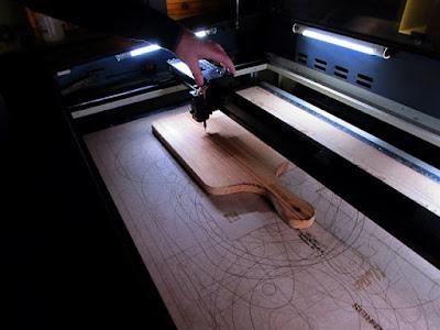 máquina À laser fazendo gravação numa tábua de madeira