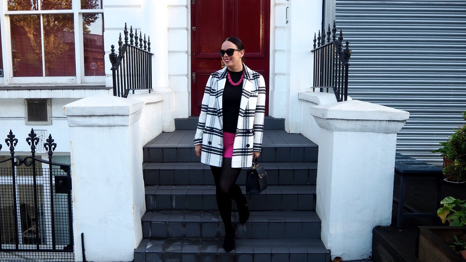 black and white checked coat with black sweater, pink bead necklace and hot pink cable knit shorts