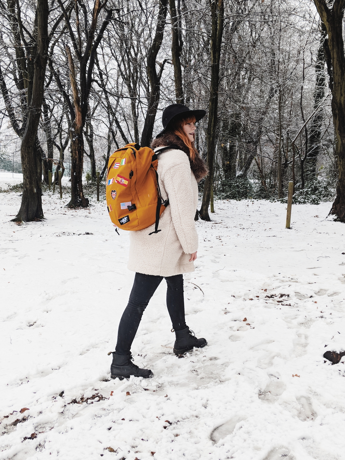 Travel blogger, Leigh Travers, walks amongst a snowy forest scene with her Cabin Zero rucksack