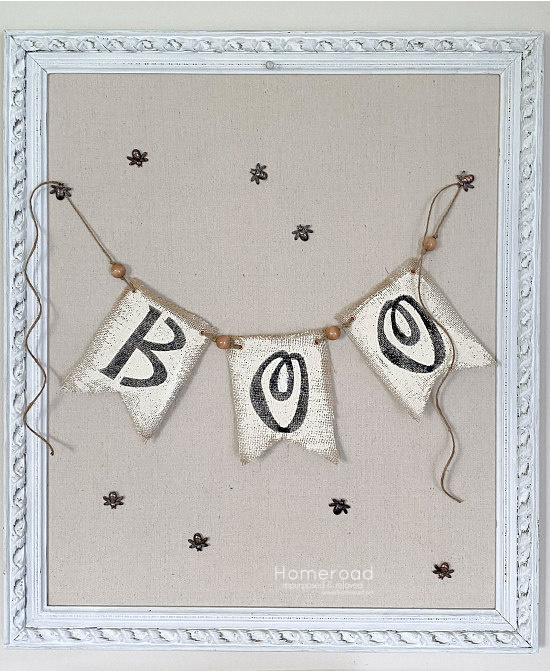 Framed bulletin board with Boo banner hanging and bee tacks