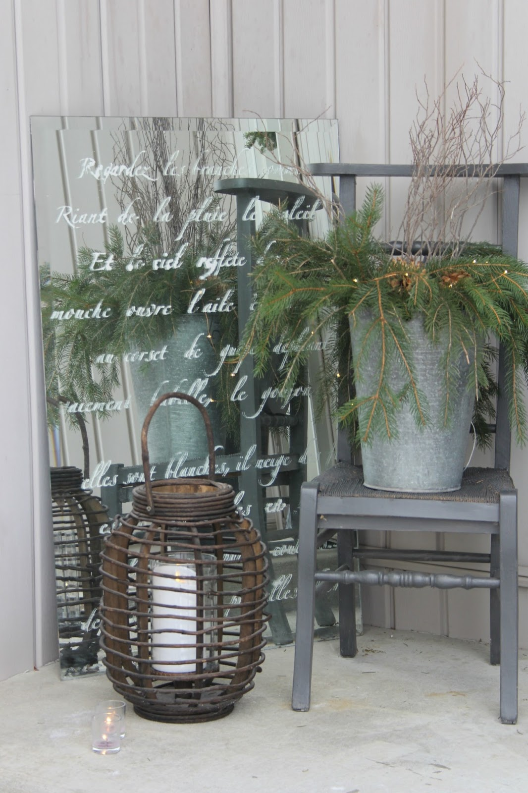 Holiday decor on front porch with stenciled mirror, lantern, and vintage chair with greenery