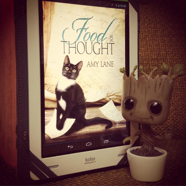 A large-headed Funko Pop bobblehead of Baby Groot stands next to a white Kobo, propped upright in its grey case. The screen holds the cover of Food For Thought, which features a small black cat against a slurry of handwritten, sepia-toned pages.