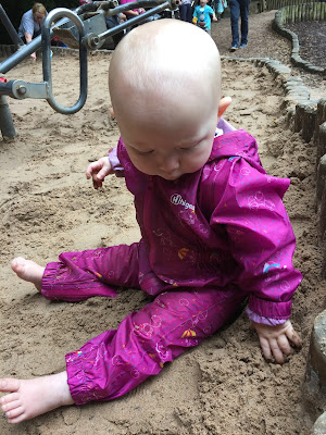 A 7 month old baby sitting in the sand in a playground and wearing a waterproof suit, but no shoes
