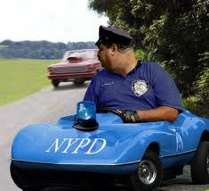 cop sits in small NYPD blue car