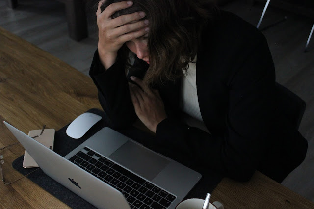 woman sat at a laptop with her head in her hands