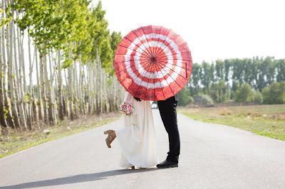 Pareja de novios en medio de una carretera detrás de una sombrilla