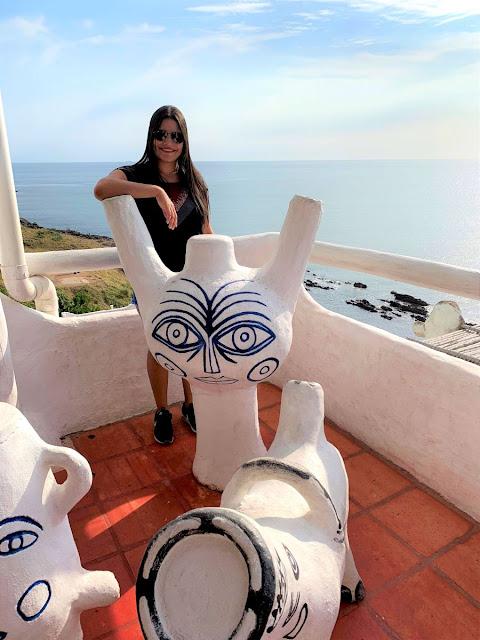 mulher jovem entre esculturas brancas de casapueblo no Uruguai