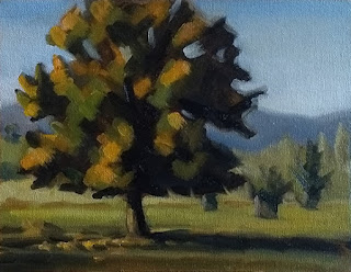 Landscape oil painting of an oak tree with distant hills.