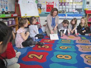 Teacher and students on rug