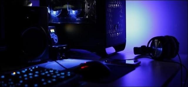 كمبيوتر سطح المكتب وسماعات الرأس على مكتب في غرفة منخفضة الإضاءة.