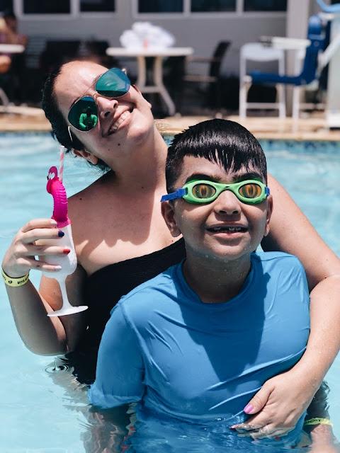 madre e hijo en una piscina tomando piña colada