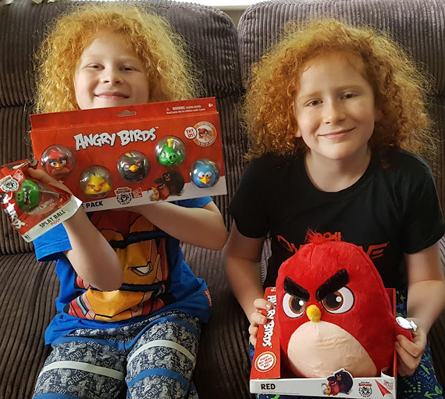 Angry Birds New Toy Range held by my 2 large boys who are sitting on the sofa smiling