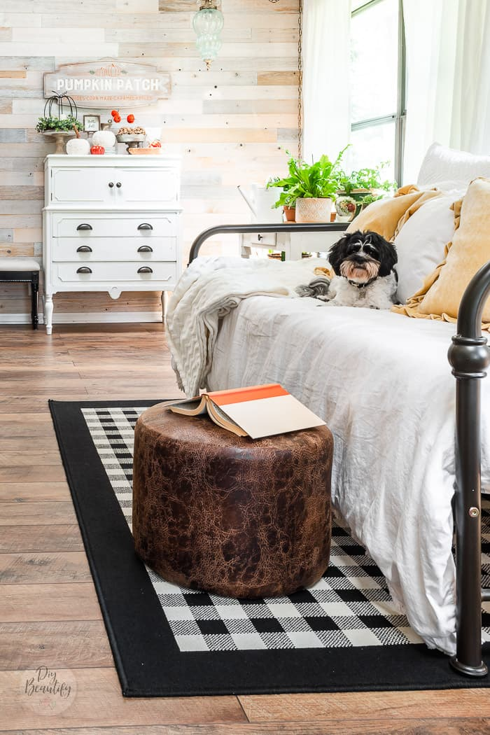 wood wall, white dresser, vintage daybed, buffalo check rug, leather ottoman, puppy