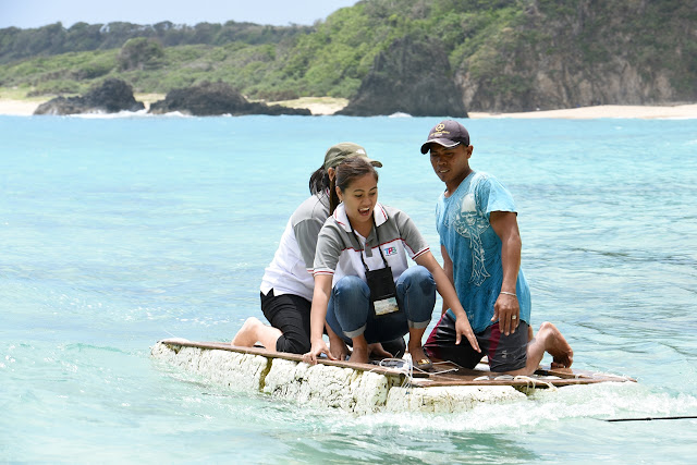 A staff of Tourism Promotions Board of the Philippines wades through the waters in Cibang Cove