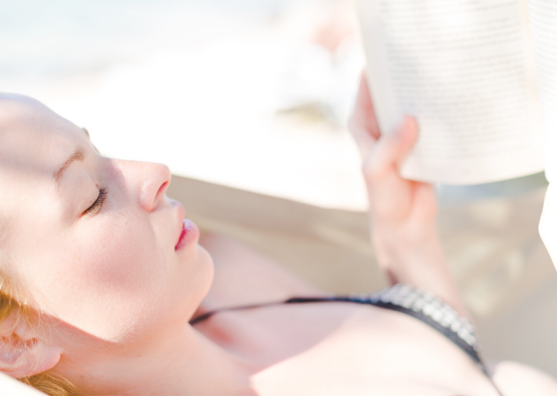 Lady reading a book in the sun in a post about 15 easy self-care ideas you can start today.