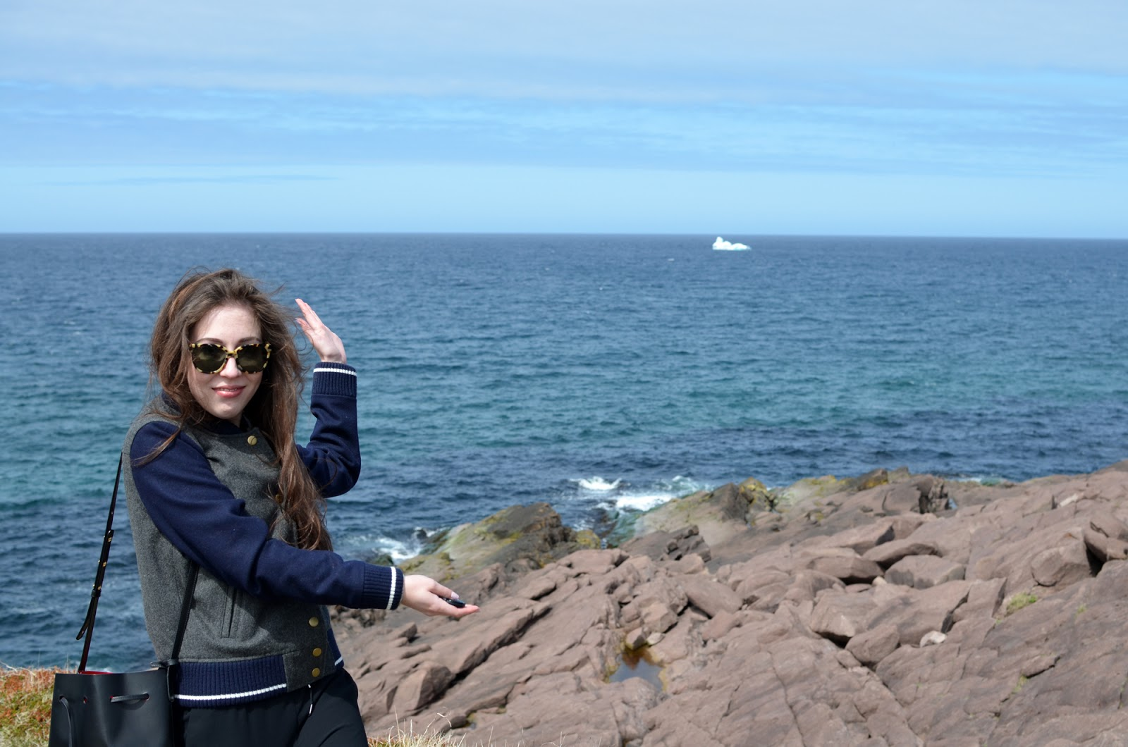 Chloe Gordon at Cape Spear with an iceberg in Newfoundland